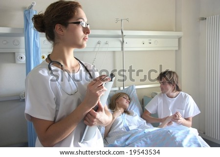 Portrait of a doctor with a her coworkers talking with a patient in the background - stock photo