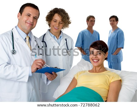 Portrait of a doctor with three of his co-workers with a patient - stock photo
