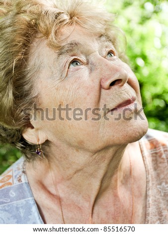 Portrait of a dreaming senior woman outdoor - stock photo