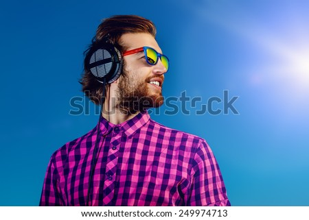 Portrait of a dreamy handsome young man listening to music in headphones. Blue sky background. Leisure, summer, vacation. - stock photo