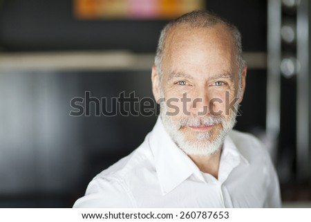 Portrait Of A Elderly Man Smiling At The Camera - stock photo