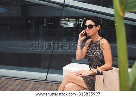 Portrait of a elegant businesswoman using smart phone in urban setting, female employed calling with smart phone while waiting for someone, elegant lady having mobile phone conversation outdoors - stock photo