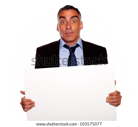 Portrait of a elegant surprised business man holding a white card with copyspace while having fun on isolated background - stock photo