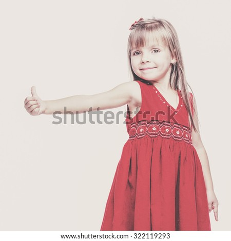 Portrait of a emotional beautiful little girl on white background showing thumbs up sign - stock photo