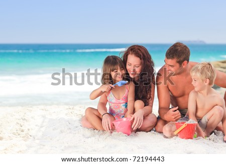 Portrait of a family at the beach - stock photo