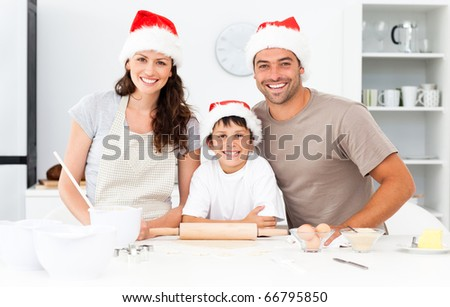 Portrait of a family cooking christmas cookies in the kitchen - stock photo