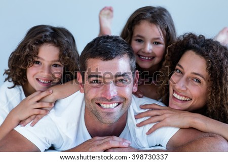 Portrait of a family lying on bed at home - stock photo