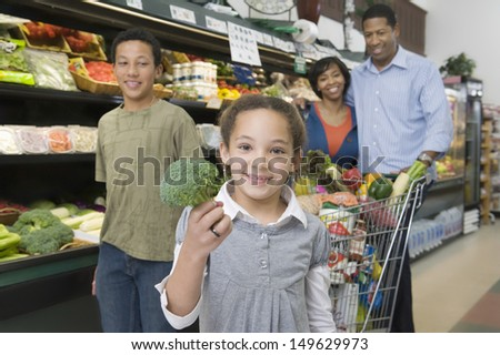 Portrait of a family of four shopping in supermarket - stock photo