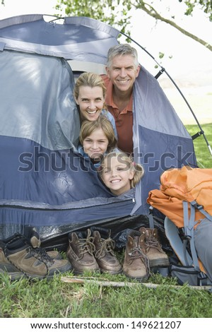 Portrait of a family of four smiling from a tent - stock photo