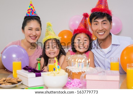 Portrait of a family of four with cake and gifts at a birthday party - stock photo