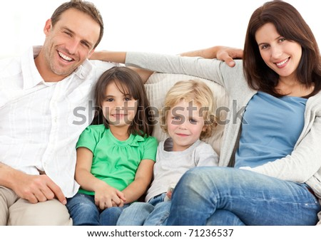 Portrait of a family on the sofa while watching television - stock photo