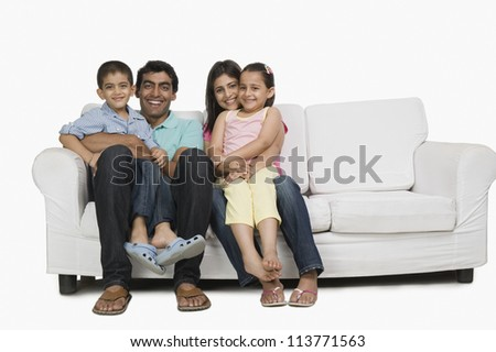Portrait of a family sitting on a couch and smiling - stock photo