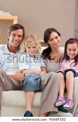 Portrait of a family watching television together in a living room - stock photo