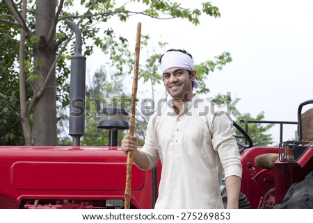 Portrait of a farmer with a stick standing next to tractor - stock photo