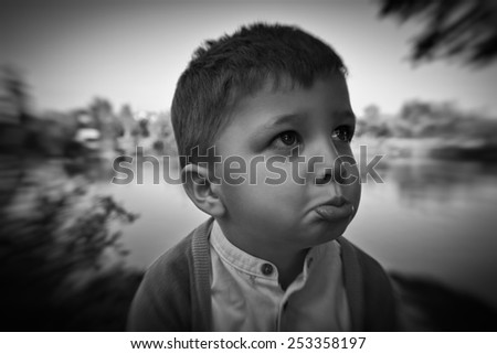 Portrait of a fashion 3 years old handsome boy, upset. Outdoor black & white picture. - stock photo