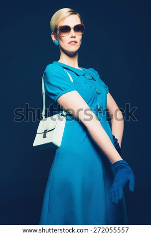 Portrait of a Fashionable Blond Woman in an Elegant Blue Dress and Gloves with Sunglasses and Shoulder Bag. Isolated on Dark Blue. - stock photo