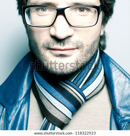 Portrait of a fashionable handsome man in blue jacket with striped scarf over light blue background. Close-up. studio shot - stock photo