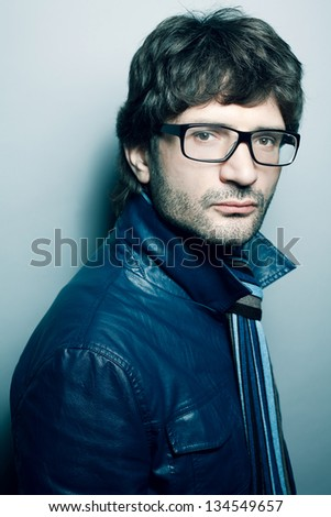 Portrait of a fashionable handsome man in blue jacket with striped scarf over light blue background. Urban style. Studio shot - stock photo