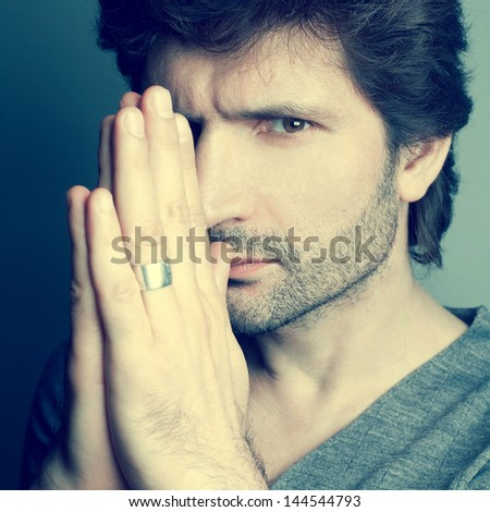 Portrait of a fashionable handsome man in gray sweater (pullover) praying over dark blue (green) background. Close up. Studio shot - stock photo