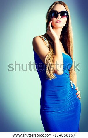 Portrait of a fashionable model in an evening dress and sunglasses. - stock photo