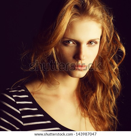 Portrait of a fashionable red-haired (ginger) model in t-shirt with black and white stripes posing over black background. Serious glance. Healthy skin & hair. Close up. Copy-space. Studio shot - stock photo