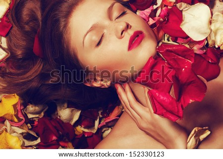 Portrait of a fashionable red-haired (ginger) model with sexy pink lips lying on fading rose petals background. Close up. Copy-space. Studio shot - stock photo