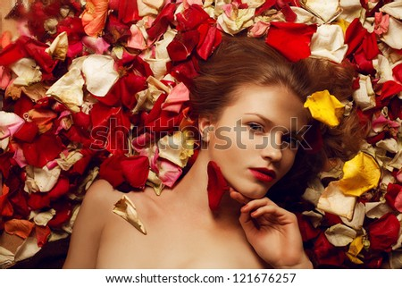 Portrait of a fashionable red-haired (ginger) model with sexy red lips lying on rose petals background and holding red petal. Studio shot - stock photo
