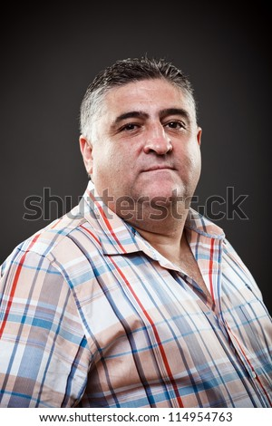 Portrait of a fat man posing in studio on gray background - stock photo