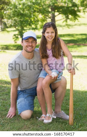 Portrait of a father and daughter holding baseball bat in the park - stock photo