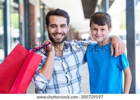 Portrait of a father and his son at the mall - stock photo
