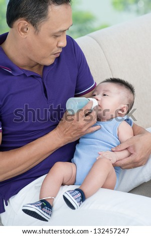 Portrait of a father feeding his son at home - stock photo