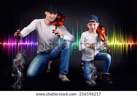 Portrait of a father with his son - posing with his violins. over Music equalizer background.  - stock photo