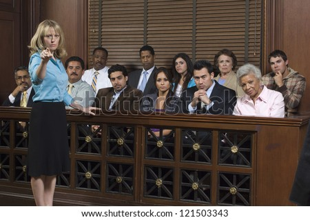 Portrait of a female advocate pointing with jurors sitting together in the witness stand at court house - stock photo