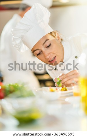 Portrait of a female cook chef. She is focused on putting herbs on a colorful plateful She is wearing white chef clothes and hat. Another man chef is cooking in the blurred background. - stock photo