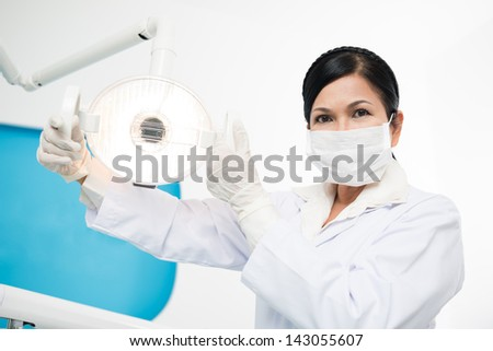 Portrait of a female dentist adjusting a dental lamp in the room - stock photo