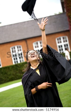 portrait of a female graduating at university throwing her hat - stock photo