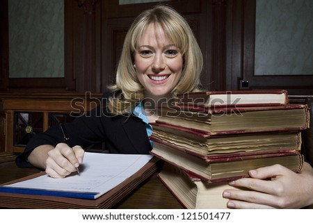 Portrait of a  female lawyer sitting with books and writing notes - stock photo