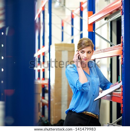Portrait of a female logistics employee on the phone and checking inventory in warehouse - stock photo