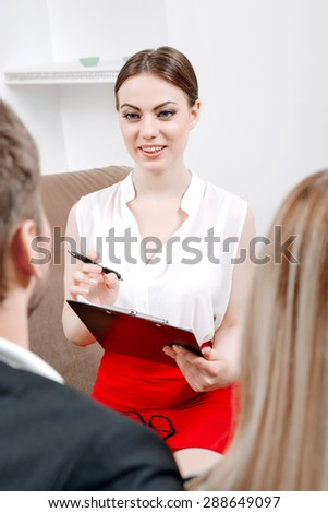 Portrait of a female psychologist wearing white blouse and glasses, explaining something and smiling to her clients young couple sitting in her office during therapy session, selective focus - stock photo