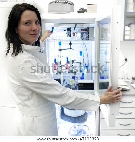 Portrait of a female researcher carrying out research experiments in a lab - researcher taking a substance from a freezer - stock photo