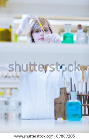 portrait of a female researcher carrying out research in a chemistry lab (color toned image; shallow DOF) - stock photo
