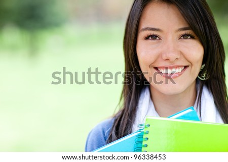 Portrait of a female student holding notebooks and smiling - stock photo
