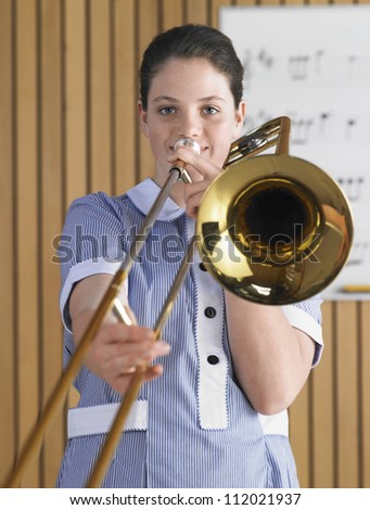 Portrait of a female student playing trombone - stock photo