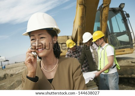 Portrait of a female surveyor in hard hat in front of workers and heavy machinery using cellphone on site - stock photo