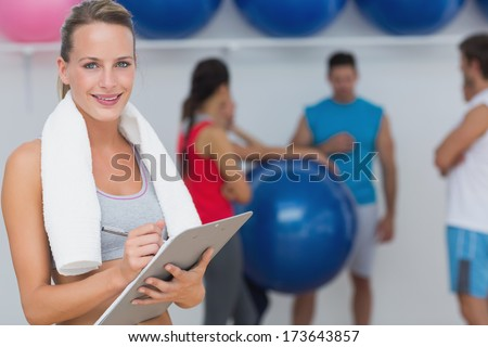 Portrait of a female trainer holding clipboard with fitness class in background at the gym - stock photo