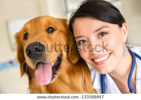 Portrait of a female vet with a cute dog - stock photo