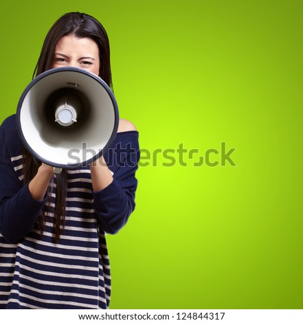 Portrait Of A Female With Megaphone On Green Background - stock photo