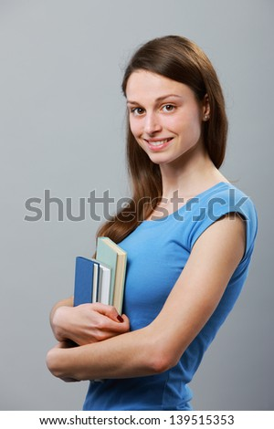 Portrait of a female young student with book - stock photo