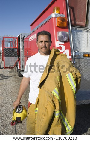 Portrait of a fire worker holding protective clothing - stock photo