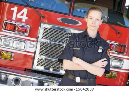 Portrait of a firefighter by a fire engine - stock photo